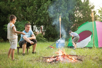 man and children making fire camping