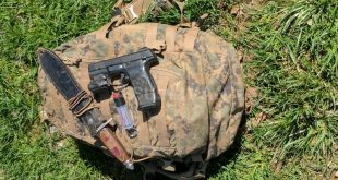 knife handgun and pepper spray on top of bug out bag