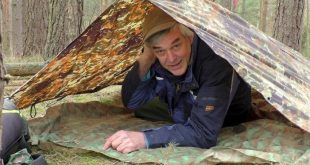 man under a tarp shelter