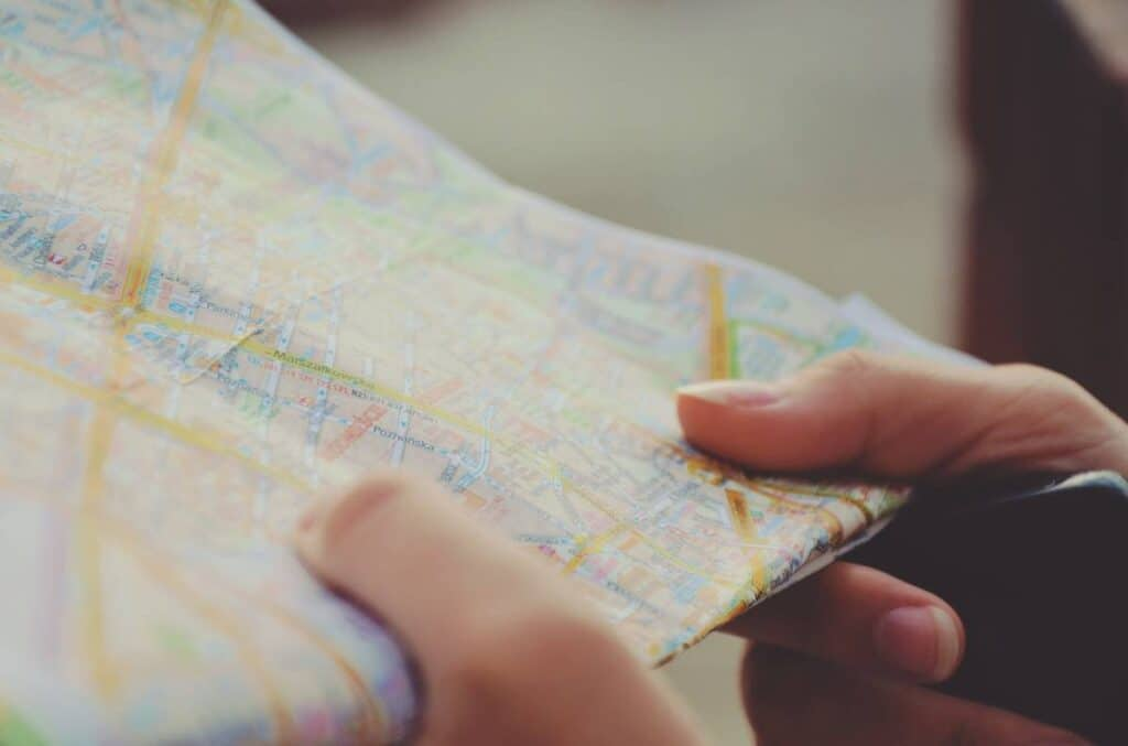 holding a paper map in hand
